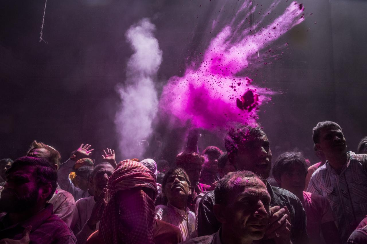 VRINDAVAN, INDIA - MARCH 26: Hindu devotees throw coloured powder during Holi celebrations at the Banke Bihari temple on March 26, 2013 in Vrindavan, India. The tradition of playing with colours on Holi draws its roots from a legend of Radha and the Hindu God Krishna. It is believed that young Krishna was jealous of Radha's fair complexion since he himself was very dark. After questioning his mother Yashoda on the darkness of his complexion, Yashoda, teasingly asked him to colour Radha's face in which ever colour he wanted. In a mischievous mood, Krishna applied colour on Radha's face. The tradition of applying color on one's beloved is being religiously followed till date. (Photo by Daniel Berehulak/Getty Images)