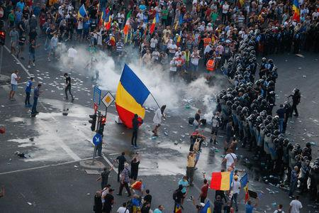 Protesters stand in front of police during a demonstration in Bucharest