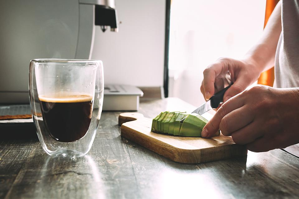Cutting avocado on a wooden cutting board with coffee cup