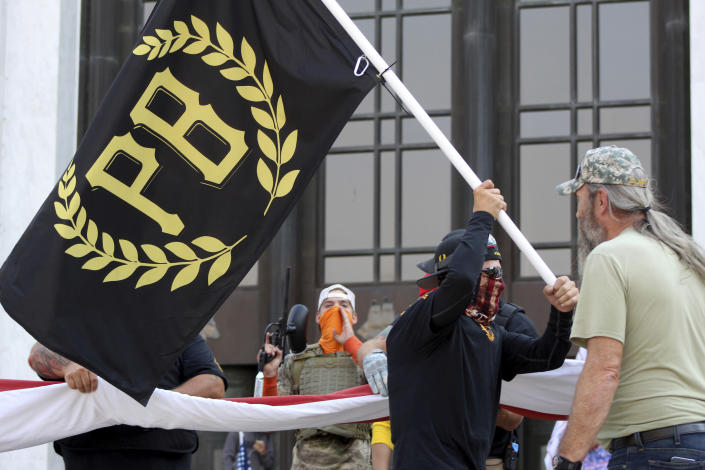 """FILE - In this Sept. 7, 2020 photo, a protester carries a Proud Boys banner, symbol of a right-wing group, while other members start to unfurl a large U.S. flag in front of the Oregon State Capitol in Salem, Ore. President Donald Trump didn't condemn white supremacist groups and their role in violence in some American cities this summer. Instead, he said the violence is a """"left-wing"""" problem and he told one far-right extremist group to """"stand back and stand by."""" His comments Tuesday night were in response to debate moderator Chris Wallace asking if he would condemn white supremacists and militia groups. Trump's exchange with Democrat Joe Biden left the extremist group Proud Boys celebrating what some of its members saw as tacit approval. (AP Photo/Andrew Selsky, File)"""