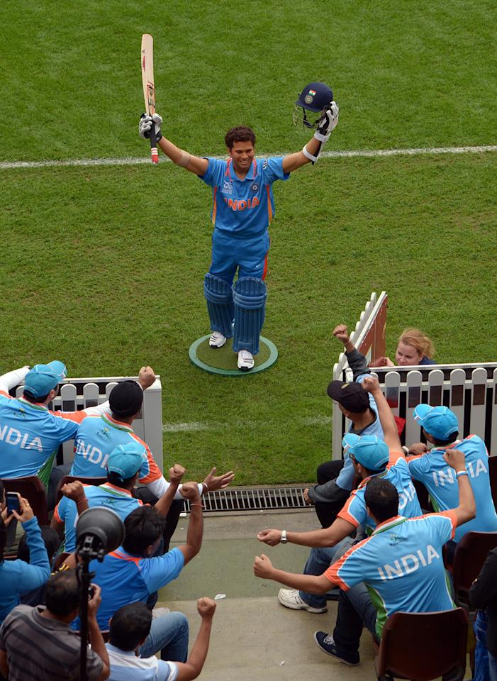 """A group of Indian cricket fans known as the """"Swami Army"""" shout in front of a wax figure of India's legendry cricket star Sachin Tendulkar, at the Sydney Cricket Ground in Sydney on April 20, 2013. The new wax figure of Tendular will be placed in the sports zone of Madame Tussauds in Sydney.                       AFP PHOTO / Saeed Khan        (Photo credit should read SAEED KHAN/AFP/Getty Images)"""