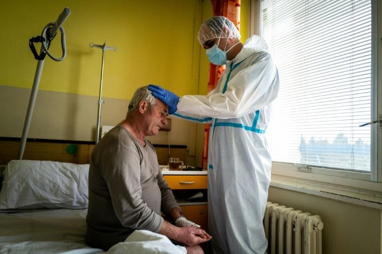 A priest prays with a Covid-19 patient at a hospital in the eastern Slovakia city of Presov