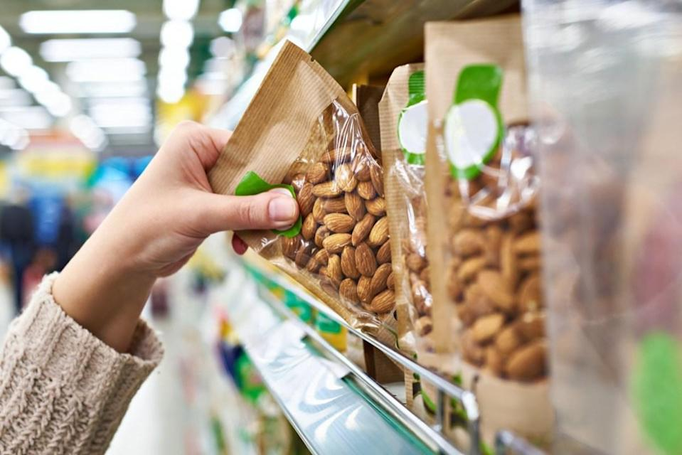 Hand of the buyer with the packaging of almond nuts in the store