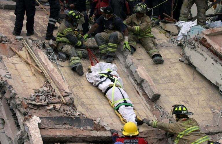 Firefighters lower a body from a building that was destroyed in Mexico City