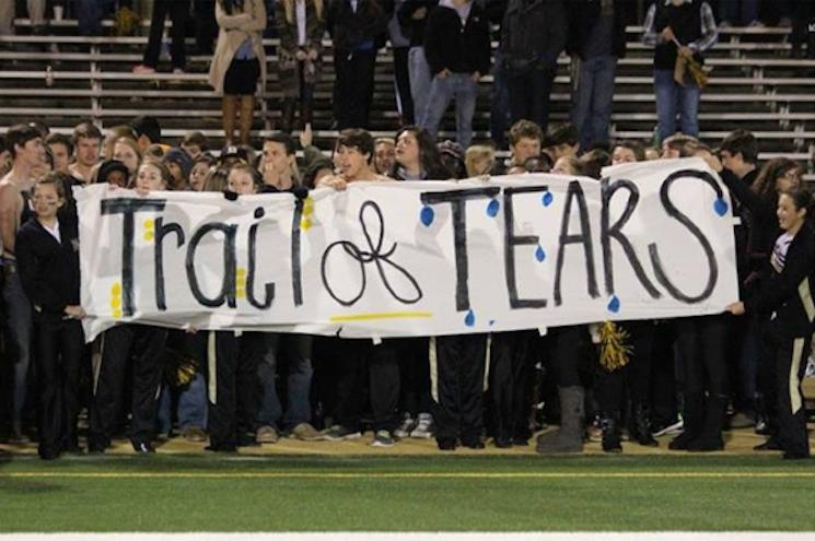 Dyersburg fans and cheerleaders hold a Trail of Tears sign belittling a foe's nickname — Facebook via Mother Jones