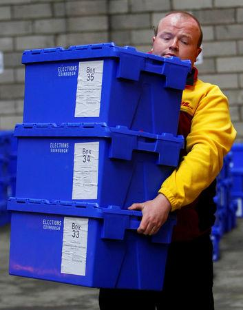 FILE PHOTO: An Edinburgh City Council contractor carries boxes of postal ballots in a storage warehouse in Edinburgh, Scotland May 5, 2010. REUTERS/David Moir/File Photo