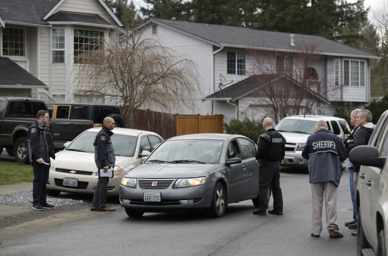 Pierce County Sheriff's Dept. deputies talks to the occupants of a passing car, Tuesday, March 13, 2018, as they stand on a street near a home (not shown) in Spanaway, Wash., where authorities say a member of the U.S. Air Force, who was stationed at Joint Base Lewis-McChord, fatally shot his two young children and their mother before killing himself overnight. (AP Photo/Ted S. Warren)
