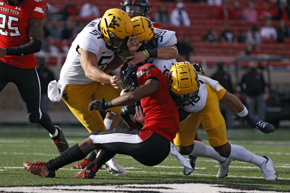 West Virginia's Jake Abbott (51) and West Virginia's Winston Wright Jr. (16) tackle Texas Tech's Adrian Frye (7) during the first half of an NCAA football game on Saturday, Oct. 24, 2020, in Lubbock, Texas. (AP Photo/Brad Tollefson)