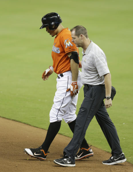 Miami Marlins' Giancarlo Stanton, left, is led off the field by team trainer Sean Cunningham, right, after straining his right hamstring in the ninth inning during a baseball game against the New York Mets, Monday, April, 29, 2013 in Miami. The Marlins defeated the Mets 4-3 in fifteen innings.(AP Photo/Lynne Sladky)