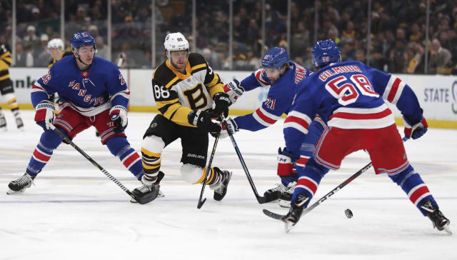 Boston Bruins right wing David Pastrnak (88) threads between New York Rangers as he pushes the puck forward during the second period of an NHL hockey game in Boston, Wednesday, March 27, 2019. From left are Rangers left wing Jimmy Vesey (26), center Brett Howden (21) and defenseman John Gilmour (58). (AP Photo/Charles Krupa)