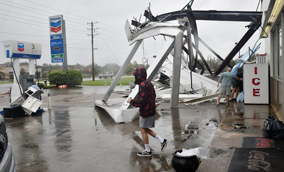 People stock up on ice and other items at a damaged convenience store after Hurricane Sally passed near Spanish Fort, Alabama.