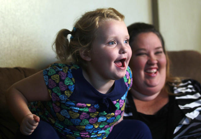 "In this photo taken Monday, Sept. 10, 2012, seven-year-old beauty pageant regular and reality show star Alana ""Honey Boo Boo"" Thompson speaks during an interview as her mother June Shannon looks on in her home in McIntyre, Ga. The round-cheeked second-grader, who previously appeared on the TLC show ""Toddlers & Tiaras,"" has a penchant for outrageous catchphrases as seen on her reality TV show, ""Here Comes Honey Boo Boo."" (AP Photo/John Bazemore)"