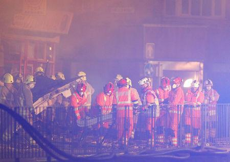 Members of the emergency services move debris at the site of an explosion which destroyed a convenience store and a home in Leicester, Britain, February 25, 2018. REUTERS/Darren Staples