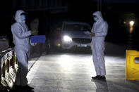 In this photo released by Xinhua News Agency, police officers in protective suits stand on duty at a temporary checkpoint in Shijiazhuang in northern China's Hebei Province on Saturday, Jan. 9, 2021. More than 360 people have tested positive in a growing COVID-19 outbreak south of Beijing in neighboring Hebei province. (Jin Haoyuan/Xinhua via AP)