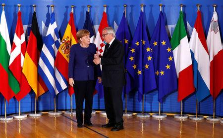 German Chancellor Angela Merkel is welcomed by European Commission President Jean-Claude Juncker at the start of an emergency European Union leaders summit on immigration at the EU Commission headquarters in Brussels, Belgium June 24, 2018.  REUTERS/Yves Herman/Pool