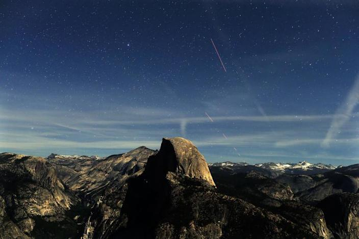 A long-exposure view of Half Dome from Glacier Point as stars appear.