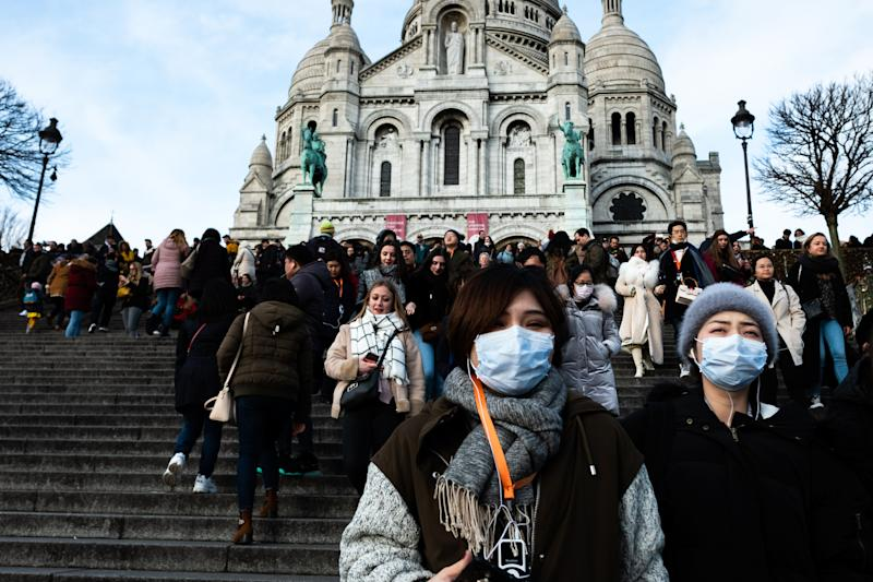Chineese tourists wear face mask near the Montmartre, Sacre Coeur in Paris, France, on 26 January 2020. (Photo by Jerome Gilles/NurPhoto via Getty Images)
