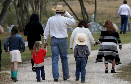 A mourner arrives with his children for the burial of Richard and Therese Rodriguez after the husband and wife were killed in the shooting at First Baptist Church of Sutherland Springs in Texas, U.S., November 11, 2017. REUTERS/Rick Wilking