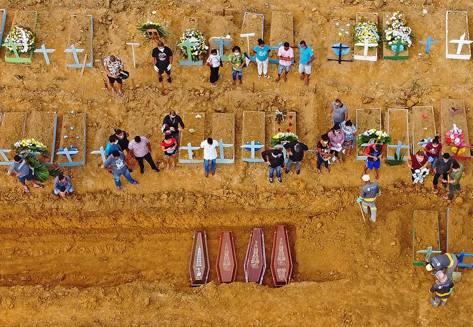TOPSHOT - Aerial picture showing a burial taking place at an area where new graves have been dug up at the Nossa Senhora Aparecida cemetery in Manaus, in the Amazon forest in Brazil, on April 22, 2020. - The new grave area hosts suspected and confirmed victims of the COVID-19 coronavirus pandemic. More than 180,000 people in the world have died from the novel coronavirus since it emerged in China last December, according to an AFP tally based on official sources. (Photo by Michael DANTAS / AFP) (Photo by MICHAEL DANTAS/AFP via Getty Images)