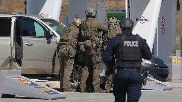 PHOTO: Royal Canadian Mounted Police officers prepare to take a suspect into custody at a gas station in Enfield, Nova Scotia, April 19, 2020. (Tim Krochak/The Canadian Press via AP)