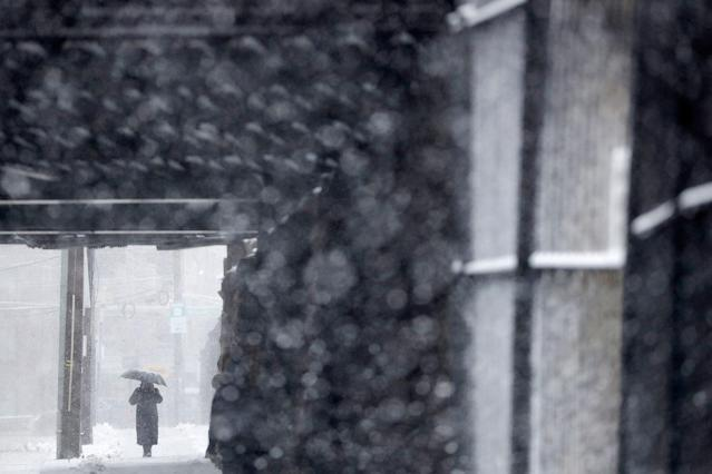 <p>A woman uses an umbrella while shielding herself from a snowstorm, Wednesday, March 21, 2018, in Hoboken, N.J. (Photo: Julio Cortez/AP) </p>