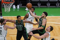 Boston Celtics forward Jayson Tatum (0) drives to the basket past Brooklyn Nets' Blake Griffin, right, as Nets guard Kyrie Irving (11) and Celtics center Tristan Thompson (13) watch during the third quarter of Game 3 in an NBA basketball first-round playoff series Friday, May 28, 2021, in Boston. (AP Photo/Elise Amendola)