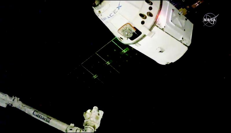 In this image taken from NASA Television, the SpaceX Dragon cargo spacecraft approaches the robotic arm for docking to the International Space Station, Saturday, Dec. 8, 2018. SpaceX delivery full of Christmas goodies has arrived at the International Space Station. The Dragon capsule pulled up at the orbiting lab Saturday, three days after launching from Cape Canaveral, Florida. It took two tries to get the Dragon close enough to be captured by the space station's robot arm. The hour-and-a-half delay was caused by trouble with the communication network that serves the space station.(NASA TV via AP)
