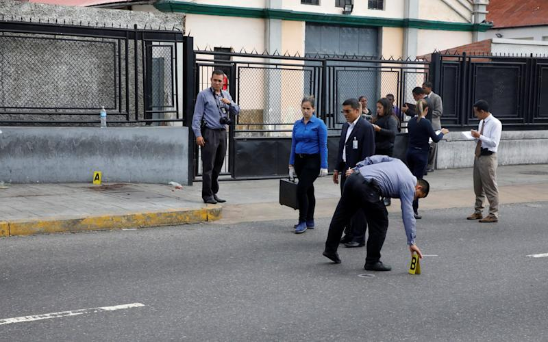 Forensic technicians stand at a crime scene where gunmen apparently shot at several people during an opposition-organised unofficial plebiscite against President Nicolas Maduro's government and his plan to rewrite the constitution, in Caracas, Venezuela July 16 - Credit: REUTERS