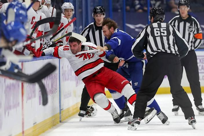 Tampa Bay Lightning's Barclay Goodrow, right, fights with Carolina Hurricanes' Jordan Martinook during the second period of an NHL hockey game Tuesday, April 20, 2021, in Tampa, Fla. (AP Photo/Mike Carlson)