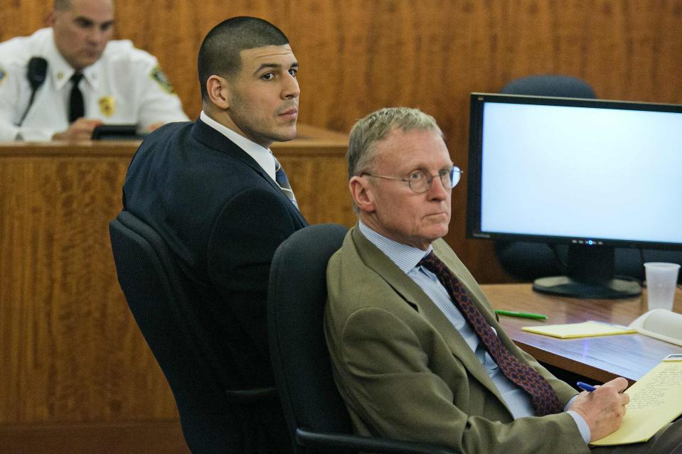 Former New England Patriots star Aaron Hernandez (L) listens to testimony with defense attorney Charles Rankin during his murder trial at the Bristol County Superior Court in Fall River, Massachusetts, February 18, 2015. Hernandez is on trial on charges of murdering semi-professional football player Odin Lloyd on June 17, 2013, the first of two murder trials he will face this year. REUTERS/Dominick Reuter/Pool (UNITED STATES - Tags: CRIME LAW SPORT FOOTBALL)