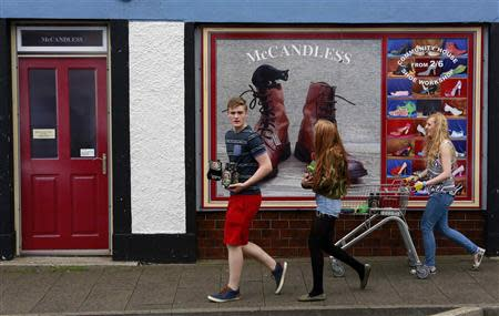 Youths walk past a shop, which has been covered with artwork to make it look more appealing, in the village of Bushmills on the Causeway Coast