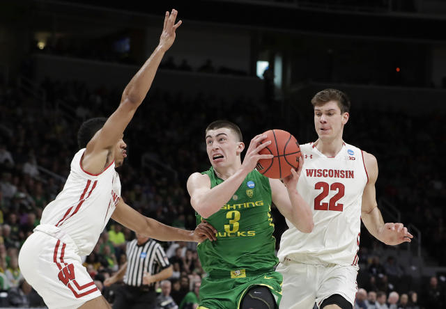 Oregon guard Payton Pritchard (3) drives between Wisconsin guard D'Mitrik Trice, left, and forward Ethan Happ (22) during the first half of a first-round game in the NCAA mens college basketball tournament Friday, March 22, 2019, in San Jose, Calif. (AP Photo/Chris Carlson)