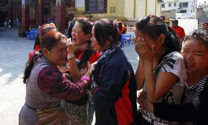 Family members of Nepalese mountaineer Ang Kaji Sherpa, killed in an avalanche on Mount Everest, cry as his body is brought to the Sherpa Monastery in Katmandu, Nepal, Saturday, April 19, 2014. Rescuers were searching through piles of snow and ice on the slopes of Mount Everest on Saturday for four Sherpa guides who were buried by an avalanche that killed 12 other Nepalese guides in the deadliest disaster on the world's highest peak. The Sherpa people are one of the main ethnic groups in Nepal's alpine region, and many make their living as climbing guides on Everest and other Himalayan peaks. (AP Photo/Niranjan Shrestha)