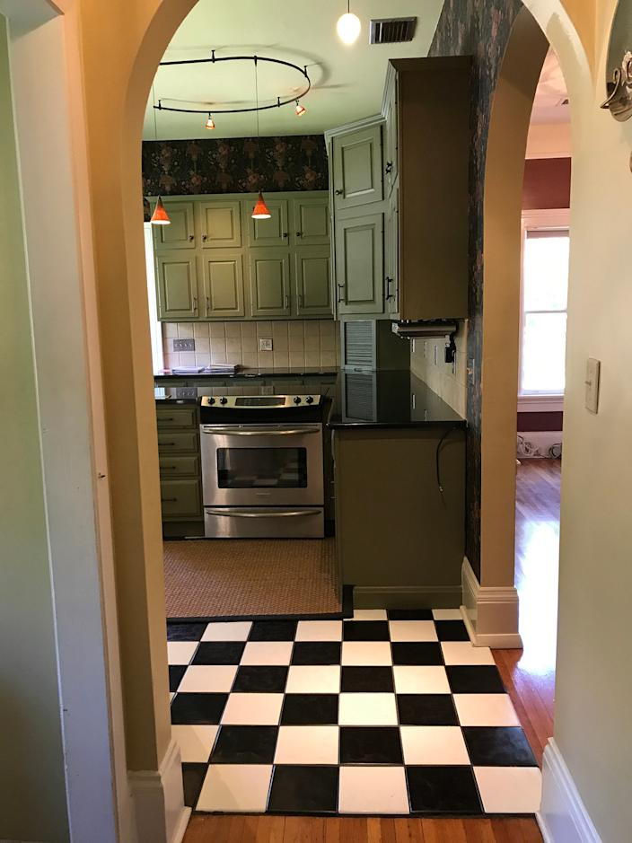 "<div class=""caption""> <strong>BEFORE:</strong> The original kitchen was covered in a checkerboard linoleum, and underneath was an unsalvageable porcelain tile. </div>"