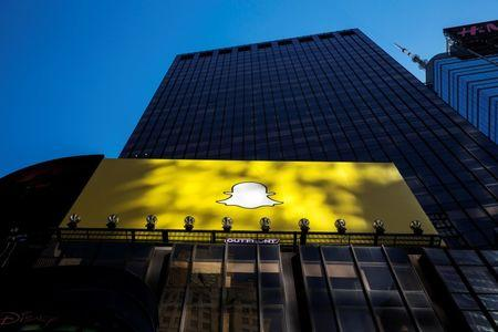 A billboard displays the logo of Snapchat above Times Square in New York