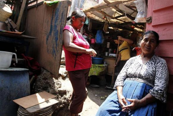 Victoria Ochante, 65, rests next to her daughter Hilda after work at her home in the shanty town Ticlio Chico in Villa Maria del Triunfo, on the outskirts of Lima, March 6, 2012.