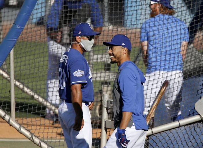 "Dodgers right fielder Mookie Betts chats with manager Dave Roberts during practice at Dodger Stadium on Friday. <span class=""copyright"">(Luis Sinco / Los Angeles Times)</span>"