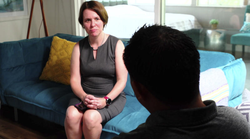 In this Aug. 7, 2019 image made from video, attorney Michelle Lapointe speaks with her client, a Guatemalan immigrant, in Santa Ana, Calif. The father is preparing to sue the federal government, alleging his 8-year-old boy was sexually molested in a foster care home funded by the U.S. Health and Human Services agency. He says he is still struggling to soothe his son's lasting nightmares, and that the 3rd grader, once talkative and outgoing, is now withdrawn and frequently says he wants to leave this world. (AP Photo/Krysta Fauria)