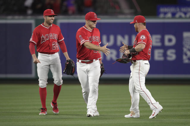 Los Angeles Angels' Peter Bourjos, Mike Trout and Kole Calhoun, from left, celebrate the team's 3-1 win against the Texas Rangers in a baseball game Friday, April 5, 2019, in Anaheim, Calif. (AP Photo/Jae C. Hong)