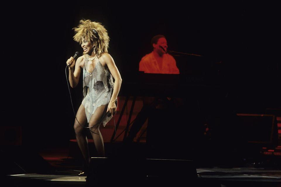 <p>Performing on stage in the 1990s in what many consider her signature look: big hair and a glitzy dress that shows of her legs.</p>