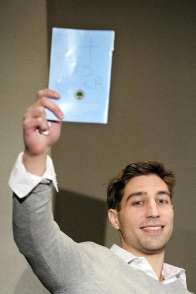 "FILE - In this Nov. 12, 2013, file photo, Ryan Ferguson displays a written message that says ""It is over"" as he speaks to members of the media during a press conference in Columbia, Mo., after his release from prison. An attorney for a Ferguson, whose conviction in the slaying of Missouri sports editor Kent Heitholt was overturned, has filed a civil rights lawsuit seeking $100 million. (AP Photo/The Columbia Daily Tribune, Nick Schnelle, File)"