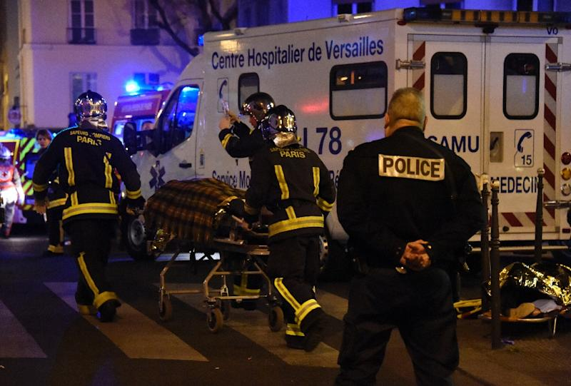 Firefighters evacuate an injured person near the Bataclan concert hall in central Paris, on November 14, 2015