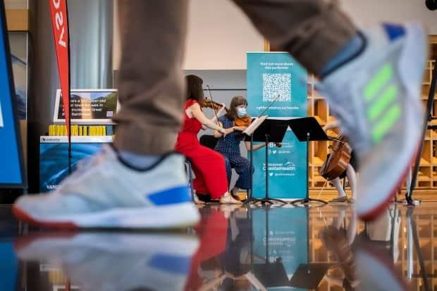 Members from the Vancouver Symphony Orchestra perform for people at the COVID-19 vaccination clinic at the Vancouver Convention Centre in Vancouver on June 24.  (Ben Nelms/CBC - image credit)