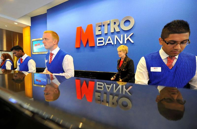 FILE PHOTO: Staff serve customers at the first branch of Metro Bank in Holborn in central London