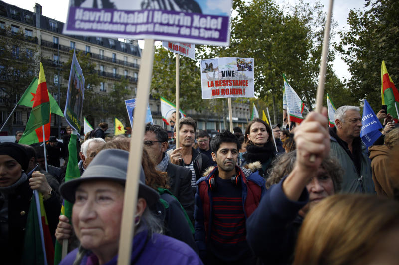 Protesters take part of a demonstration against Turkey's offensive in northern Syria, on Republique plaza in eastern Paris, Saturday, Oct. 19, 2019. Demonstrators warned that the offensive could allow Islamic State extremists to resurge. Kurdish forces being targeted by Turkey this week were crucial to the international campaign against IS extremists, who orchestrated several deadly attacks against France. (AP Photo/Thibault Camus)