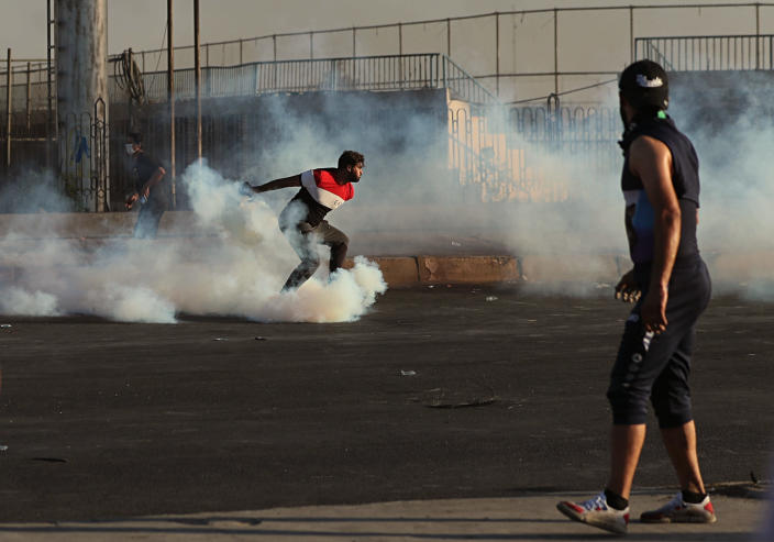 A protester throws back the smoke bomb back towards riot police during a demonstration in Baghdad, Iraq, Saturday, Oct. 5, 2019. The spontaneous protests which started Tuesday in Baghdad and southern cities were sparked by endemic corruption and lack of jobs. Security responded with a harsh crackdown, leaving more than 70 killed. (AP Photo/Hadi Mizban)