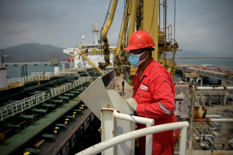 A worker of Venezuelan state oil company PDVSA watches the Iranian oil tanker Fortune dock at El Palito refinery