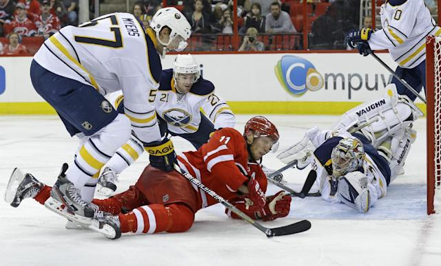 Carolina Hurricanes' Jordan Staal (11) tries to score as Buffalo Sabres goalie Ryan Miller (30), Tyler Myers (57) and Drew Stafford (21) defend the goal during the second period of an NHL preseason hockey game in Raleigh, N.C., Friday, Sept. 27, 2013. (AP Photo/Gerry Broome)