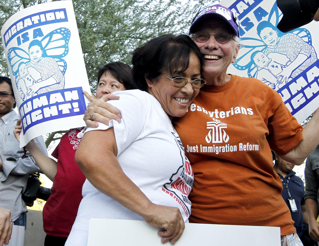 """Maria Jesus Rodriguez, left, gets a hug from Selena Keesecker, after Rodriguez spoke about her story as they join dozens who rally in front of U.S. Immigration and Customs Enforcement building, a day after a portion of Arizona's immigration law took effect, Wednesday, Sept. 19, 2012, in Phoenix. Civil rights activists contend will lead to systematic racial profiling, as the protesters chanted """"No papers, no fear."""" (AP Photo/Ross D. Franklin)"""