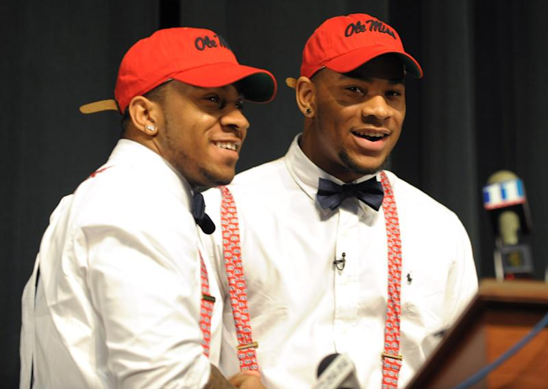 Grayson High School football player Robert Nkemdiche, right, the nation's top recruit, is congratulated by his brother Denzel during Robert Nkemdiche's announcement to play college football for Ole Miss, at a Grayson, Ga., signing ceremony Wednesday Feb. 6, 2013. Denzel Nkemdiche also plays for the Rebels. (AP Photo/David Tulis)
